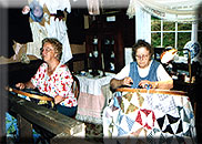Picture of two women quilting a colorful quilt