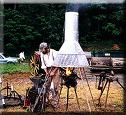 Picture of man demonstarting old-style welding with old-style furnace